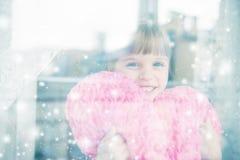 Das kleine Mädchen, das ein Herz hält, formte Kissen und das Lächeln Lizenzfreie Stockfotografie