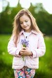 Das kleine Mädchen, das ein Purpur riecht, blüht im Frühjahr Park Lizenzfreie Stockbilder