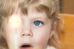 Das kleine Mädchen, das eine Kerze mit ihrem breiten Mund betrachtet, öffnen sich Lizenzfreie Stockbilder