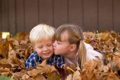 Das kleine Mädchen, das einen kleinen Jungen legt in Blattstapel küsst, verlässt lizenzfreies stockfoto