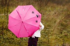 Das kleine Mädchen, das ich unter einem rosa Regenschirm im Herbstpark mich versteckte Lizenzfreie Stockfotografie