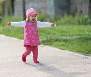 Das kleine Mädchen, das mit den Armen lacht, streckte aus Stockbilder