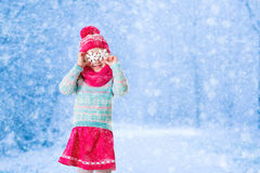Das kleine Mädchen, das mit Spielzeugschnee spielt, blättert im Winterpark ab Stockfoto