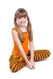 Das kleine Mädchen, das orange Kleid trägt, sitzt lizenzfreies stockfoto