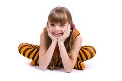 Das kleine Mädchen, das orange Kleid trägt, sitzt lizenzfreie stockbilder