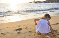 Das kleine Mädchen, das am Sonnenuntergang nahe dem Meer spielt Lizenzfreie Stockfotografie