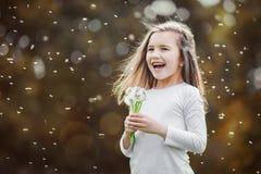 Das kleine Mädchen, das weißer Löwenzahn im Herbst riecht, parken Lizenzfreie Stockfotos