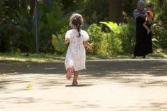 Das kleine Mädchen, das zu ihrer Mutter laufen und der Bruder auf einem Schmutz schleppen in einem Park Lizenzfreies Stockbild