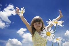 Das kleine Mädchen in den camomiles Stockfoto