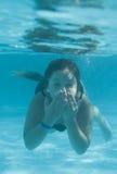 Das kleine Mädchen in der Hotelpoolschwimmen Unterwasser und im Lächeln Stockbilder