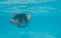 Das kleine Mädchen in der Hotelpoolschwimmen Unterwasser und im Lächeln Stockbild