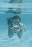 Das kleine Mädchen in der Hotelpoolschwimmen Unterwasser und im Lächeln Lizenzfreie Stockfotografie