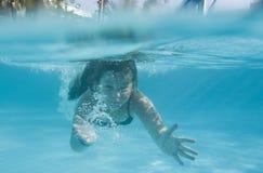 Das kleine Mädchen in der Hotelpoolschwimmen Unterwasser und im Lächeln Lizenzfreie Stockfotos