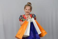 Das kleine Mädchen, der Käufer hält die farbigen Einkaufstaschen Lizenzfreie Stockfotografie
