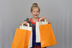 Das kleine Mädchen, der Käufer hält die farbigen Einkaufstaschen Stockfotografie