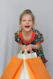Das kleine Mädchen, der Käufer hält die farbigen Einkaufstaschen Lizenzfreie Stockfotos