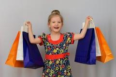 Das kleine Mädchen, der Käufer hält die farbigen Einkaufstaschen Lizenzfreies Stockfoto