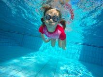Das kleine Mädchen in der Wasserparkschwimmen Unterwasser und im Lächeln lizenzfreie stockfotos