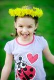 Das kleine Mädchen in einem Kranz vom gelben Löwenzahn Lizenzfreie Stockfotografie