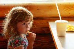 Das kleine Mädchen in einem Sommercafé lizenzfreie stockbilder