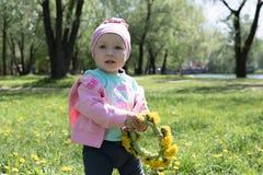 Das kleine Mädchen, das einen Kranz des Löwenzahns hält, blüht stockfotos