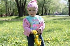 Das kleine Mädchen, das einen Kranz des Löwenzahns hält, blüht lizenzfreie stockfotografie