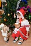 Das kleine Mädchen in einer Klage des kleinen Rotkäppchens mit Spielzeug Santa Claus über einen Baum des neuen Jahres Stockfotografie