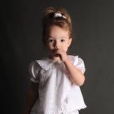 Das kleine Mädchen gegen einen dunklen Hintergrund lacht Lizenzfreie Stockfotos
