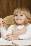 Das kleine Mädchen hält einen Bleistift in seiner Hand an Stockfotografie