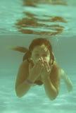 Das kleine Mädchen im Hotelpoolschwimmen Underwater und dem smilin Stockbild