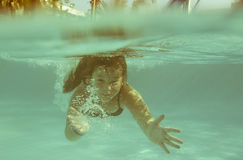 Das kleine Mädchen im Hotelpoolschwimmen Underwater und dem smilin Stockfotos