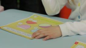 Das kleine Mädchen, das im Kindergarten studiert stock footage