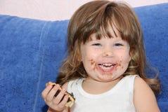 Das kleine Mädchen isst einen Kuchen Stockbilder
