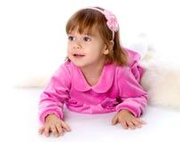 Das kleine Mädchen liegt auf einem Fußboden lizenzfreie stockbilder