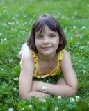 Das kleine Mädchen liegt auf einem grünen Rasen. Lizenzfreies Stockbild