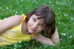 Das kleine Mädchen liegt auf einem Rasen Lizenzfreies Stockfoto