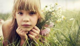 Das kleine Mädchen liegt in der Wiese Lizenzfreie Stockfotos