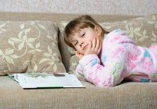 Das kleine Mädchen liest das Buch, das auf einem Sofa liegt Lizenzfreies Stockbild