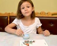 Das kleine Mädchen malt mit Farben eine Vogelzufuhr lizenzfreie stockbilder