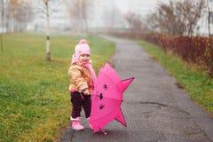Das kleine Mädchen mit einem Regenschirm im Fall Lizenzfreies Stockbild