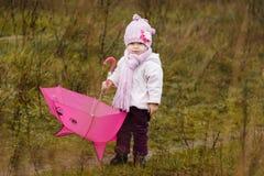 Das kleine Mädchen mit einem Regenschirm im Fall in Herbst Stockfoto
