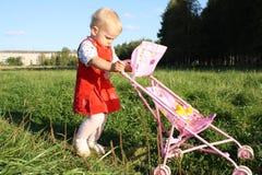 Das kleine Mädchen mit einem Wagen. Lizenzfreie Stockbilder