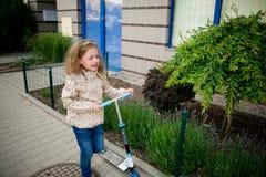 Das kleine Mädchen rollt den Roller auf dem Bürgersteig und schreit bitterlich Lizenzfreies Stockfoto