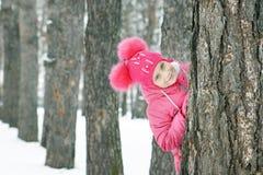 Das kleine Mädchen, das rosa Kleidung trägt, schaut heraus von einem Kieferstamm draußen im Winter Lizenzfreies Stockfoto