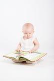 Das kleine Mädchen schaut das Buch der Kinder Stockbilder