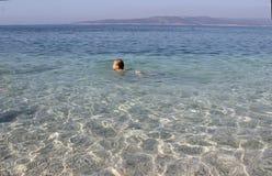 Das kleine Mädchen schwimmt im haarscharfen Meer kroatien lizenzfreie stockfotografie