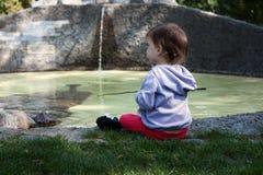 Das kleine Mädchen sitzt auf dem Ufer des Teichs lizenzfreie stockfotos