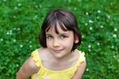 Das kleine Mädchen sitzt auf einem grünen Rasen Lizenzfreies Stockbild