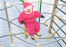 Das kleine Mädchen sitzt auf einem Spielplatz der Kinder Lizenzfreies Stockbild