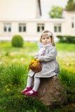 Das kleine Mädchen sitzt auf einem Stein mit einem Blumenstrauß des Löwenzahns Lizenzfreie Stockbilder